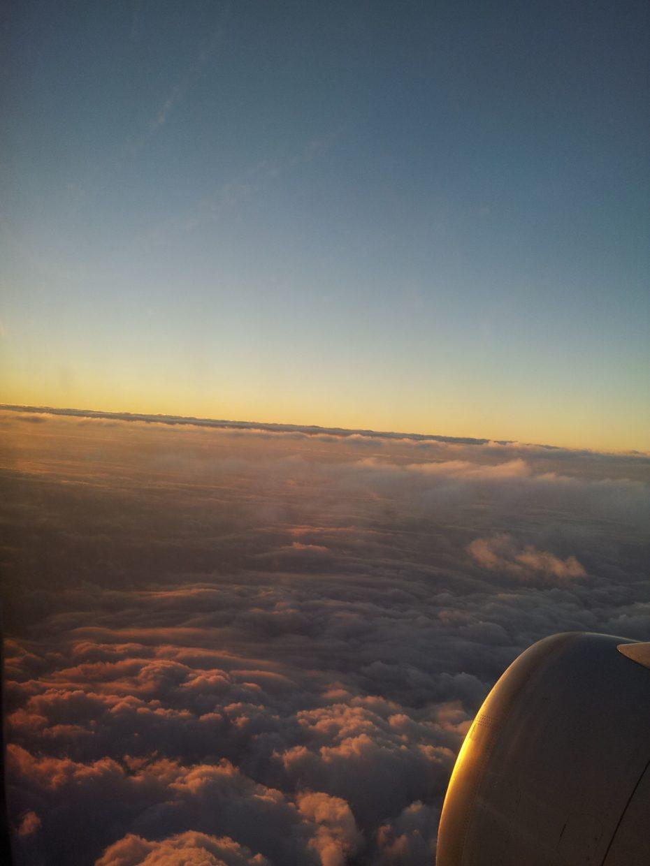 Ala de avión en un cielo nubloso durante el amanecer.