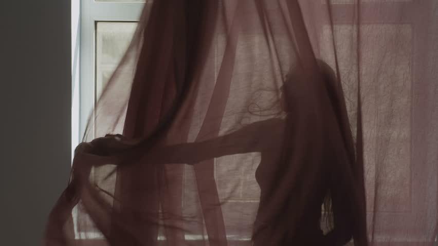 mujer sujetando cortina